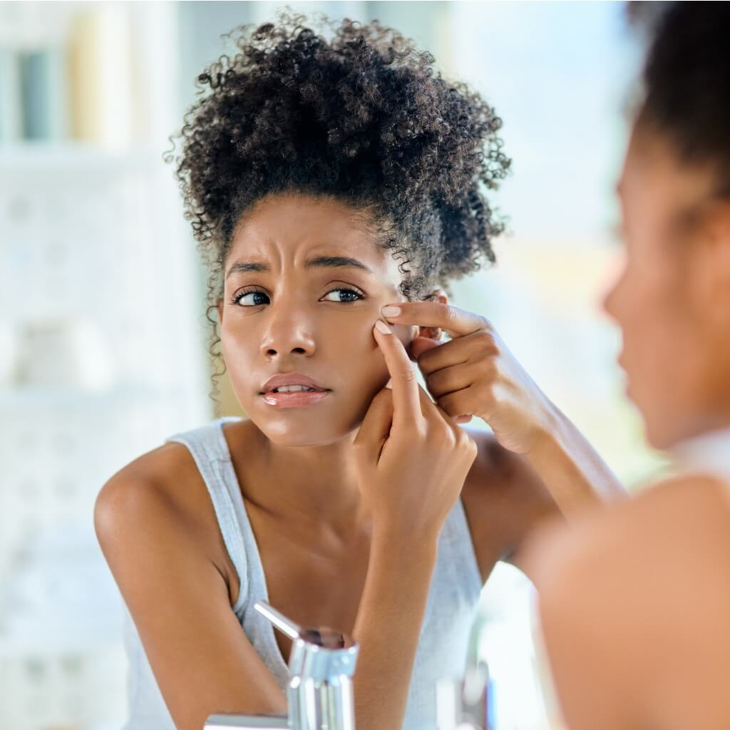 Woman Checking For Acne Using Mirror